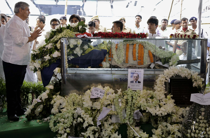 Former Board of Control for Cricket in India (BCCI) President Sashank Manohar, left, pays tribute to the body of Jagmohan Dalmiya, in glass casket, BCCI president and former International Cricket Council chief during his funeral in Kolkata, India, Monday, Sept. 21, 2015. Dalmiya, the top sports administrator credited with making India a major financial power in cricket, was admitted to a hospital in Kolkata on Thursday following a cardiac arrest. He died Sunday, Sept. 20, 2015, at the age of 75. (AP Photo/Bikas Das)