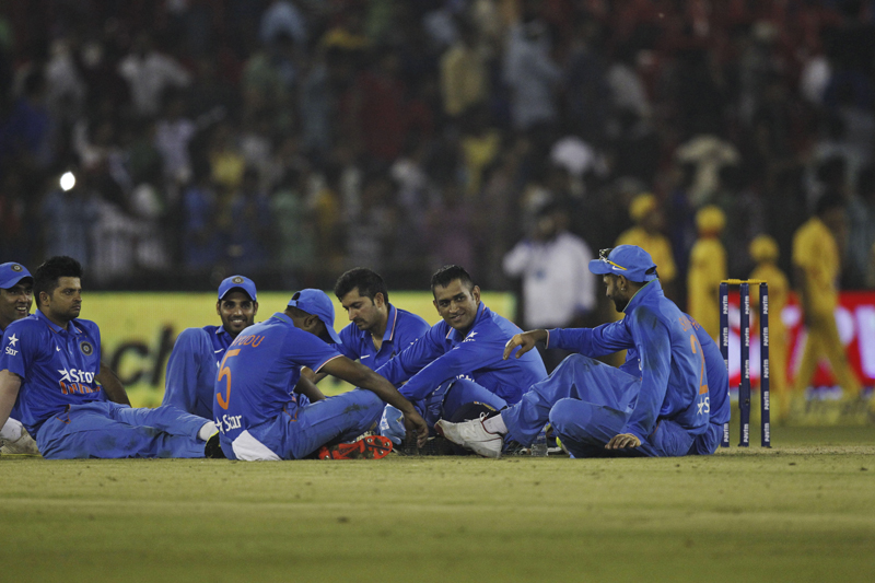 Indian players sit in the ground as their second Twenty20 cricket match against South Africa is disrupted after spectators threw water bottles in Cuttack, India, Monday, Oct. 5, 2015. (AP Photo/Biswaranjan Rout)