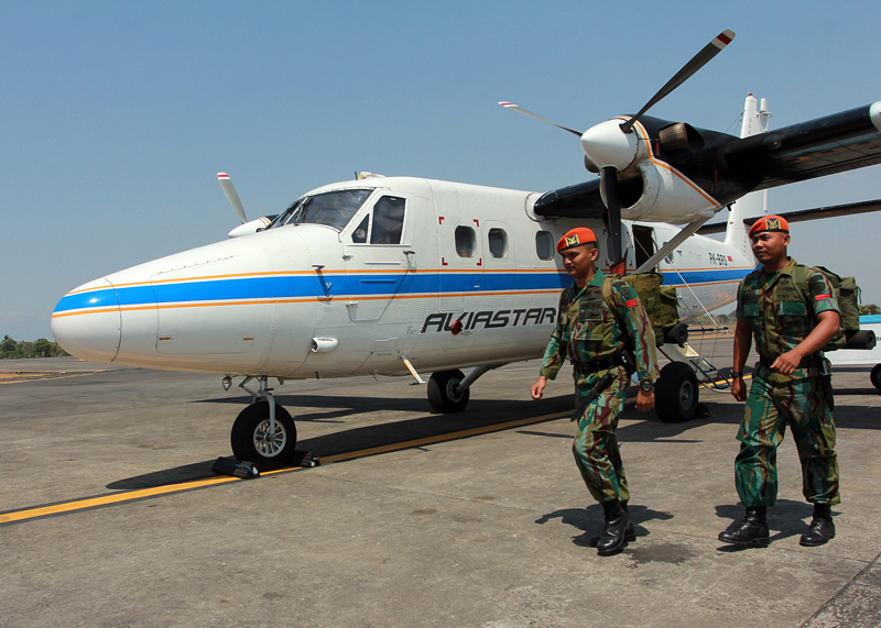 Military personnel walk past a Twin Otter plane similar to the on that is reported missing on Friday, at Sultan Hasanuddin airport in Makassar, South Sulawesi, Indonesia, Saturday, Oct. 3, 2015.  An air and ground search is underway Saturday for a small passenger plane that went missing with 10 people on board during a domestic flight in eastern Indonesia. (AP Photo/Masyudi S. Firmansyah)