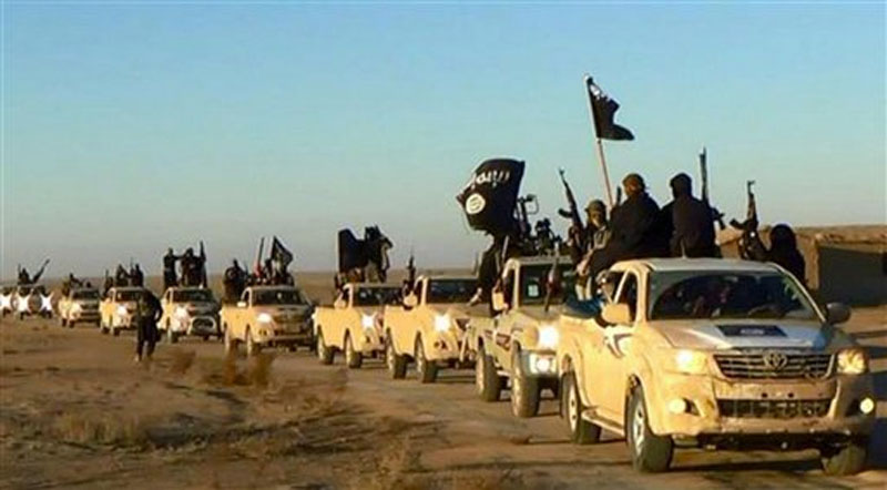 Militants of the Islamic State group hold up their weapons and wave its flags on their vehicles in a convoy on a road leading to Iraq, while riding in Raqqa city in Syria. Photo: AP