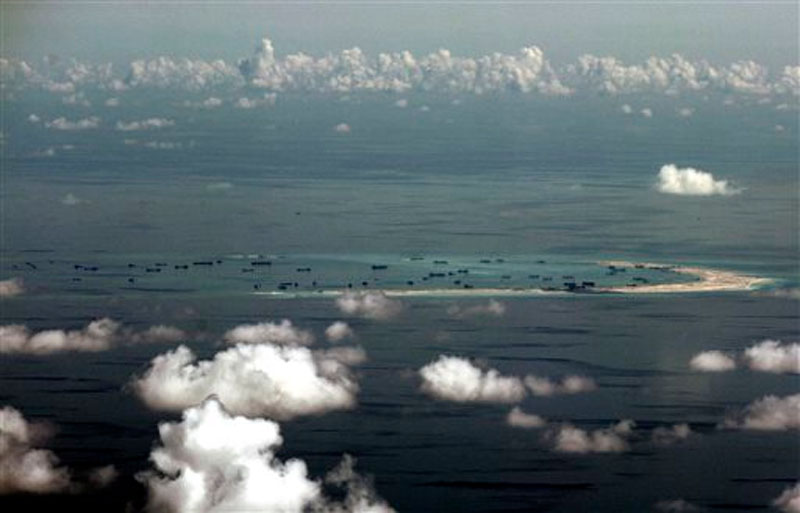 An aerial photo taken through a glass window of a military plane shows China's alleged on-going reclamation of Mischief Reef in the Spratly Islands in the South China Sea on May 11, 2015. Photo: AP
