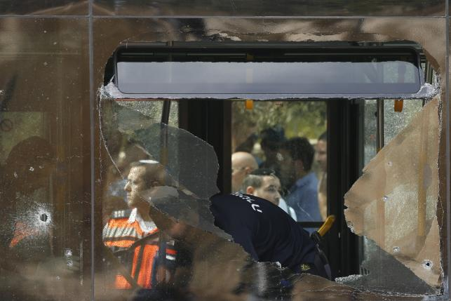 An Israeli police officer stands near a shattered window aboard a bus after an attack in Jerusalem October 13, 2015. REUTERS/Ronen Zvulun