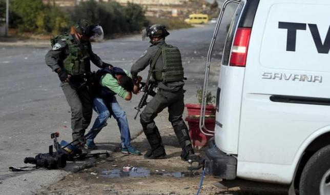 Israeli border policemen beat a Palestinian journalist during clashes with Palestinian protesters near the Jewish settlement of Bet El, near the West Bank city of Ramallah October 30, 2015. REUTERS/Mohamad Torokman