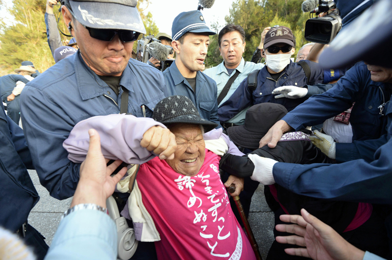 One of the protesters against the relocation of US Marine Air Station Futenma is carried away in front of the gate of Camp Schwab, an American base near the planned relocation site, in Nago, Okinawa Prefecture Thursday, October 29, 2015. Photo: Kyodo News via AP