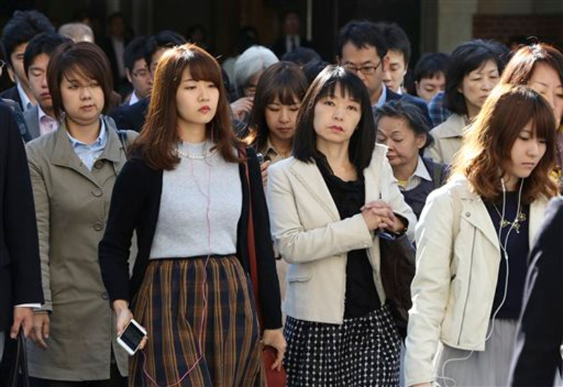 Commuters cross a street during morning rush hour in Tokyo. The central government exceeded its 30 percent target for hiring of women for career-track positions, raising the rate to 34 percent this year from 24 percent last year, according to the latest Cabinet Office data. Two years after Prime Minister Shinzo Abe made womenu2019s advancement a top policy priority, statistics suggest Japanu2019s male-dominated workplaces have evolved slightly, but also highlight the deep-seated societal forces keeping the gender gap alive on Monday, Oct. 26, 2015. Photo: AP