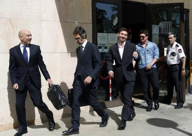 Barcelona's soccer player Lionel Messi (centre) gives a thumbs up as he leaves after answering charges of tax evasion in a court in Gava September 27, 2013. Photo: Reuters