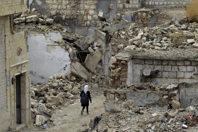A school girl walks past damaged buildings in the rebel-controlled area of Maaret al-Numan town in Idlib province, Syria October 28, 2015. REUTERS/Khalil Ashawi