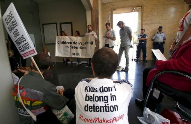Police watch a group of around twenty protesters occupy Australian Prime Minister Malcolm Turnbull's electoral office, demanding the end to the policy of offshore detention of asylum seekers, in the Sydney suburb of Edgecliff, Australia, October 14, 2015.  REUTERS/David Gray