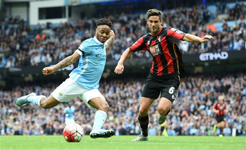 Manchester City's Raheem Sterling (left), scores his side's fourth goal of the game to complete his hat-trick, past Bournemouth's Andrew Surman, during their English Premier League soccer match at The Etihad Stadium, Manchester, England, Saturday, October 17, 2015. Photo: AP