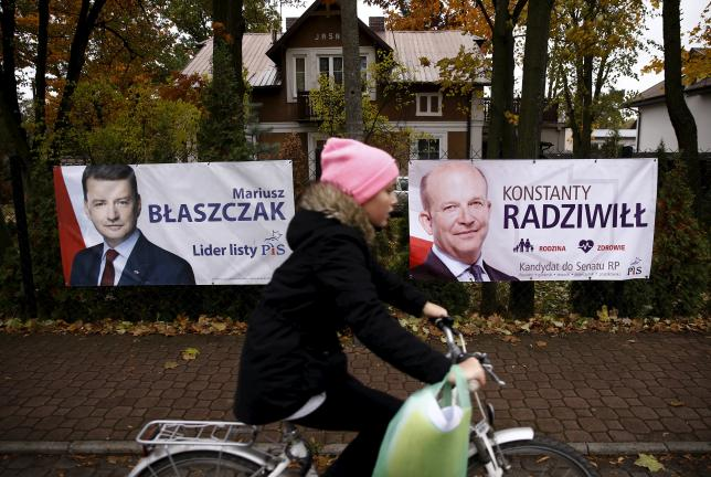 A child cycles in front of the election posters of Law and Justice candidates Mariusz Blaszczak (L) and Konstanty Radziwill (R) in Milanowek, outskirts of Warsaw, Poland October 23, 2015. REUTERS/Kacper Pempel
