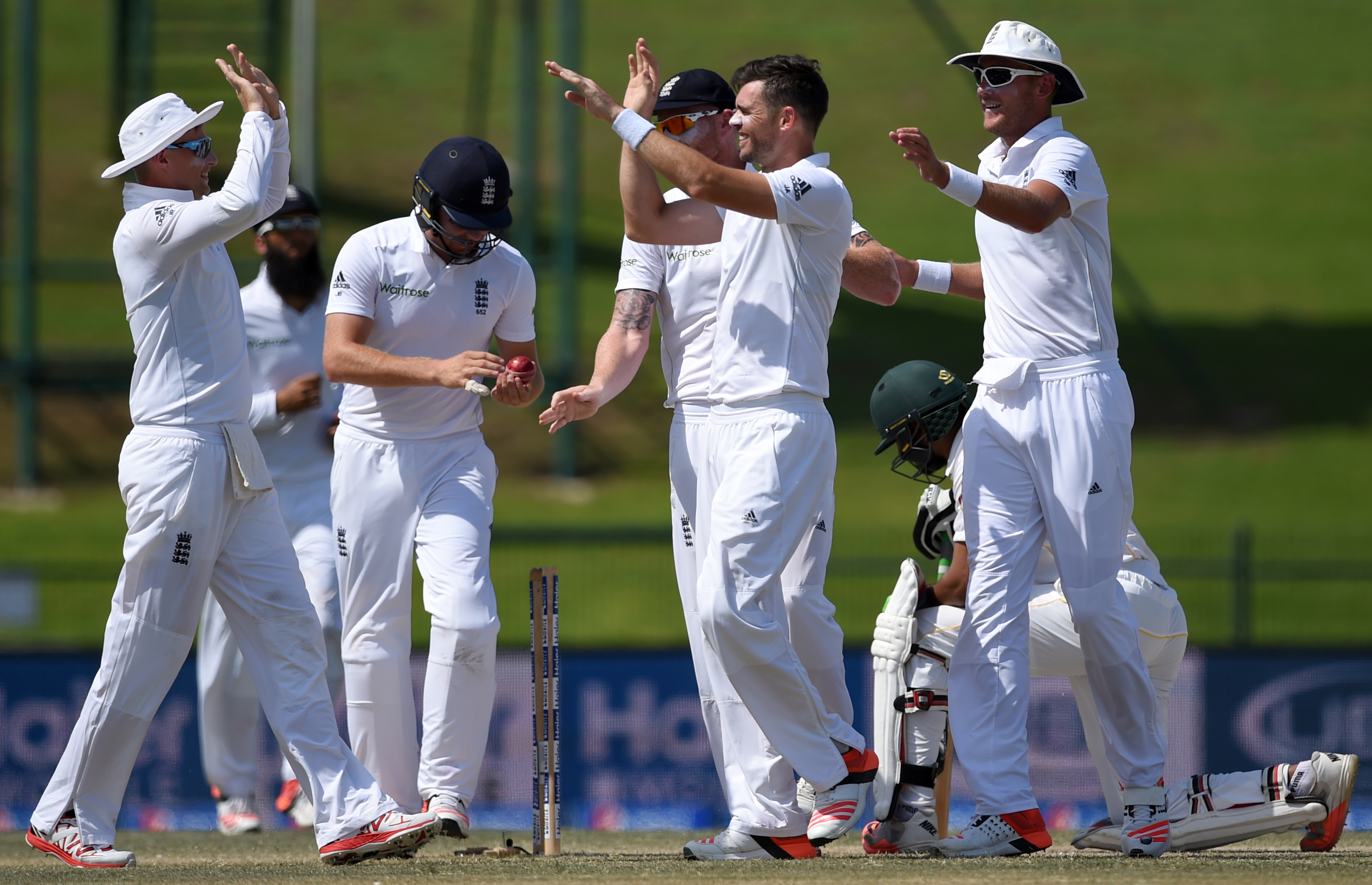 England's James Anderson, centre, and teammates celebrate after Pakistan's Shan Masood dismissal in second innings during the final day of first test match between Pakistan vs England at Zayed Cricket Stadium in Abu Dhabi, United Arab Emirates, Saturday, Oct.17, 2015. (AP Photo/Hafsal Ahmed)