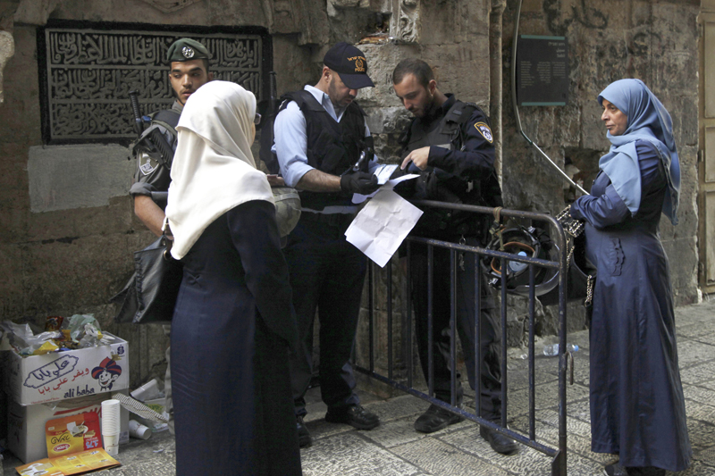 Israeli police check the papers of a Palestinian woman in Jerusalem's Old City Thursday, Oct. 8, 2015.  Israeli Prime Minister Benjamin Netanyahu has barred all Cabinet ministers and lawmakers from visiting a sensitive Jerusalem holy site, fearing any high-profile spectacle could further enflame tensions that have gripped the country for weeks, an Israeli official said Thursday. The Jerusalem hilltop compound lies at the heart of recent tensions. It's revered by Muslims as the spot where Prophet Muhammad ascended to heaven and by Jews as the site of the two Jewish biblical Temples. (AP Photo/Mahmoud Illean)