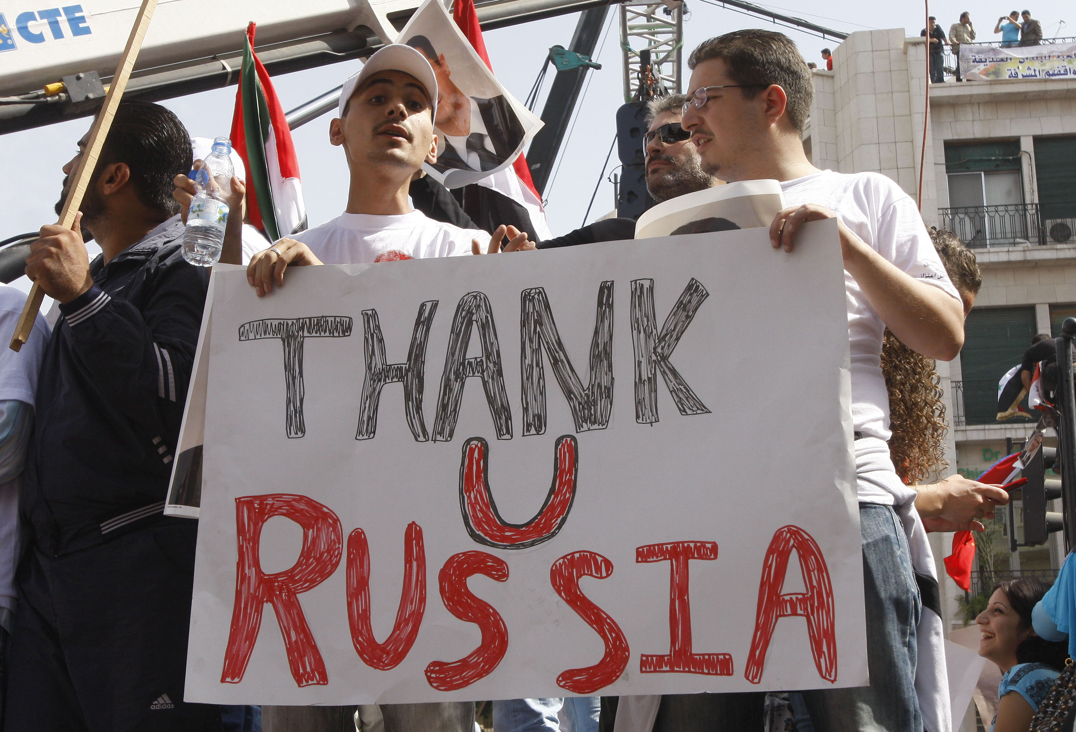 FILE - In this Oct. 12, 2011 file photo, supporters of the Syrian government hold a pro-Russian banner as they show their support for Syrian President Bashar Assad and to thank Russia and China for blocking a U.N. Security Council resolution condemning Syria for its brutal crackdown, during a demonstration in Damascus, Syria. Russian President Vladimir Putin is winning plaudits from many Syrians and Iraqis, who see Russia's military intervention in Syria as a turning point after more than a year of largely ineffectual efforts by the U.S.u0096led coalition battling the Islamic State group. (AP Photo/Muzaffar Salman, File)