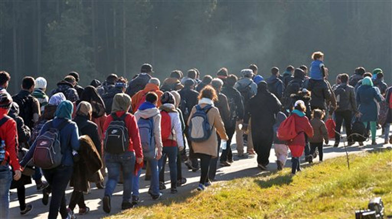 Migrants walk along a road after crossing the border between Austria and Germany in Wegscheid near Passau on Wednesday, October 28, 2015. Photo: AP