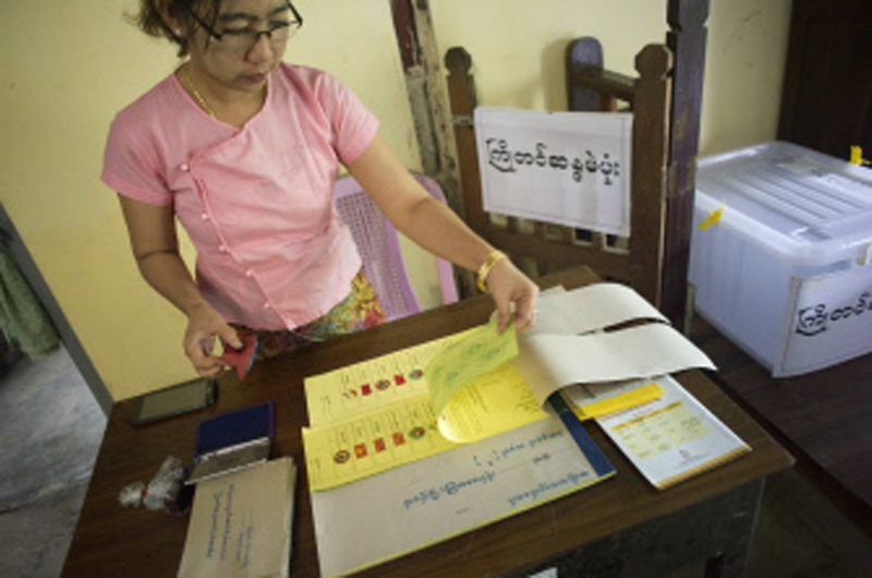 A member of staff at a polling station preparing for advance voting at a ward administration office on the outskirts of Yangon, on Thursday.  Photo: AFP
