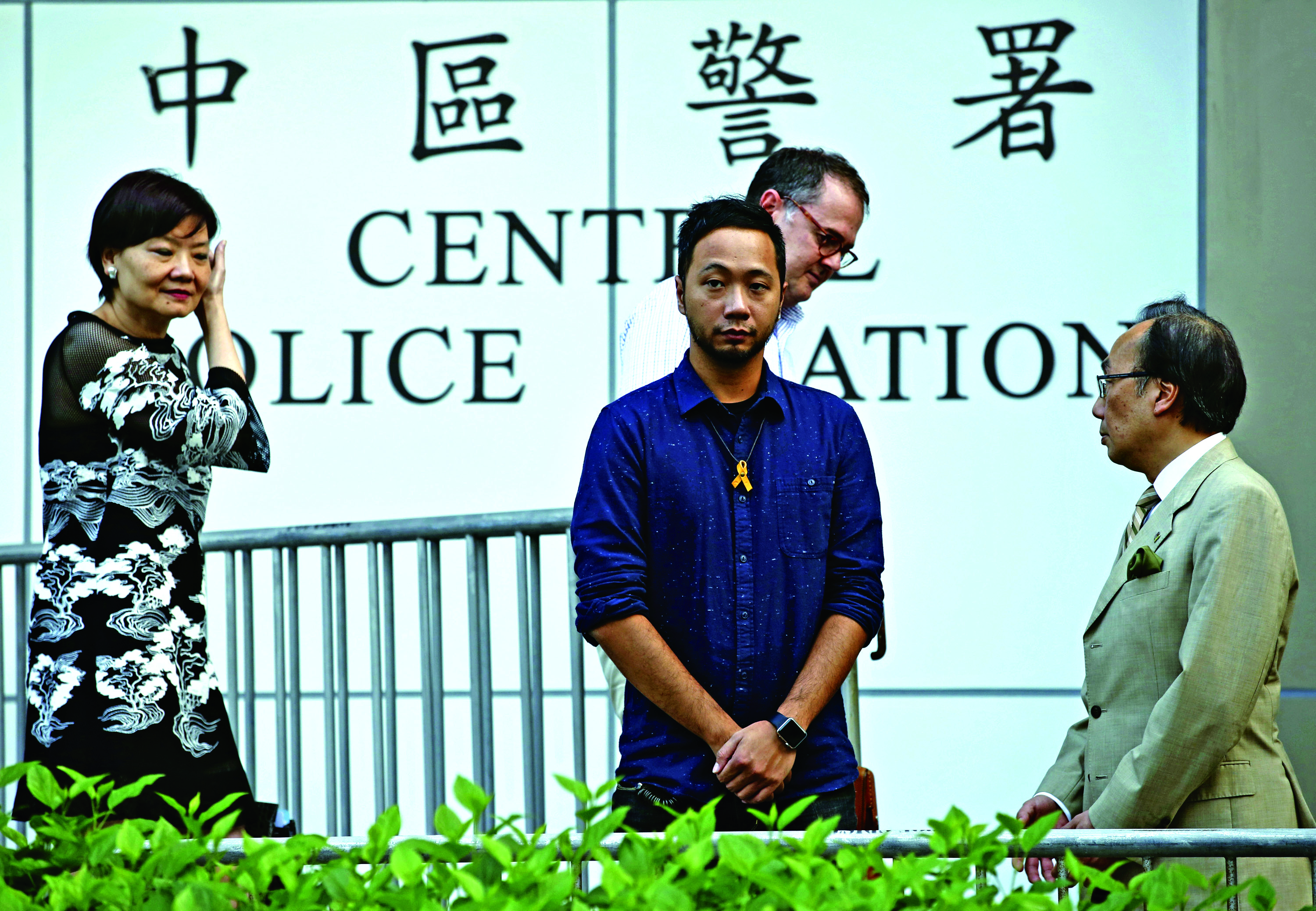 The activist, Ken Tsang, center, reports to a police station in Hong Kong, Thursday, Oct. 15, 2015. Hong Kong police on Thursday charged seven officers with harming an activist who was beaten in a filmed confrontation that stirred outrage among city residents at the height of the pro-democracy protests last year. (AP Photo/Kin Cheung)