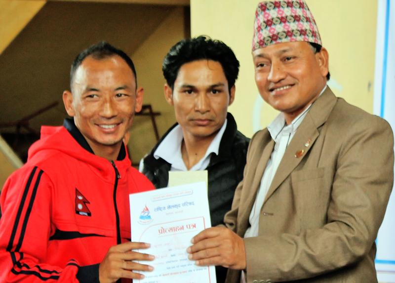 National Sports Council (NSC) Member Secretary Keshab Kumar Bista (right) handing over a felicitation letter to karateka Sunil Lama at a programme on Sunday. Courtesy: NSC