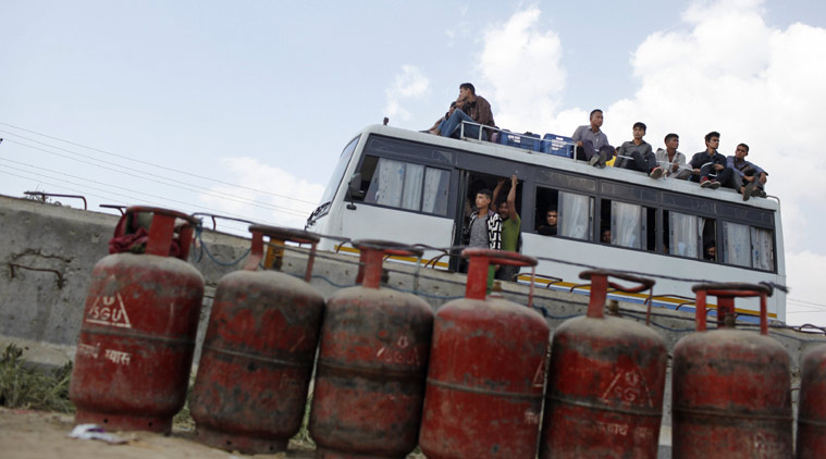 File- People sit on top of a crowded bus as it passes near lined cooking gas cylinders in Kathmandu, Nepal, Monday, October 19, 2015. Photo: AP