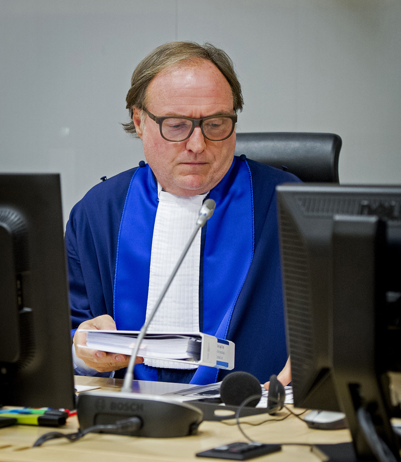 Judge Cuno Tarfusser of Italy opens the court session as Ahmad Al Mahdi Al Faqi waits in the court room for his initial appearance at the International Criminal Court in The Hague, Netherlands, Wednesday, Sept. 30, 2015. Al Faqi, an alleged Islamic radical, is the first suspect in the court's custody charged with the war crime of deliberately attacking and destroying religious or historical monuments in Timbuktu, Mali. (AP Photo/Robin van Lonkhuijsen, Pool)