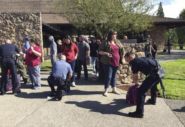 Police officers inspect bags as students and staff are evacuated from campus following a shooting incident at Umpqua Community College in Roseburg, Oregon October 1, 2015. REUTERS/Michael Sullivan/The News-Review