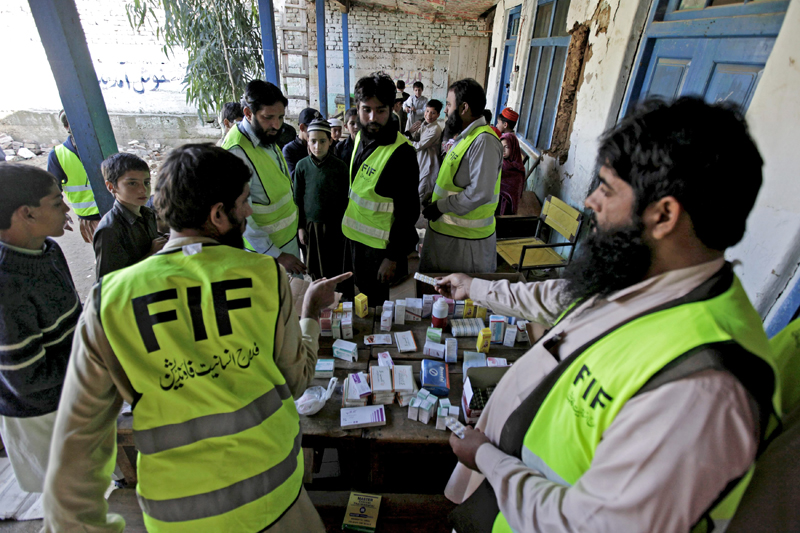 Volunteers distribute free medicine to people affected by the earthquake at a medical camp set up by the Jamaat-ud-Dawa organisation in the Rehankot village in district Upper Dir, Pakistan, October 28, 2015. Photo: Reuters
