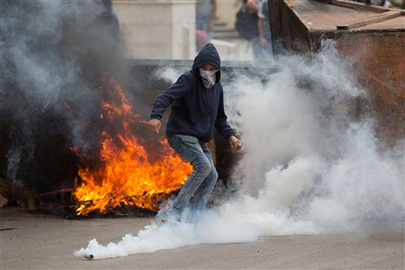 Palestinian kicks a tear gas canister during clashes with Israeli troops near Ramallah, West Bank, Saturday, Oct. 10, 2015. Photo: AP
