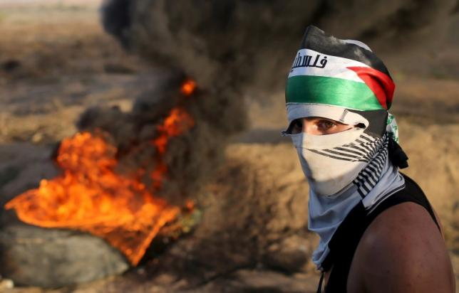 A masked Palestinian protester passes by burning tyres during clashes with Israeli troops near the border between Israel and Central Gaza Strip October 14, 2015.  REUTERS/Ibraheem Abu Mustafa