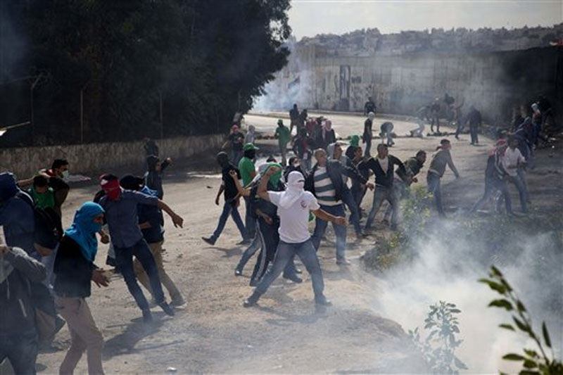 Palestinian students hurl stones at Israeli troops over the separation barrier during clashes following a protest near the Al-Quds University in the West Bank village of Abu Dis, near Jerusalem, Wednesday, October 28, 2015. Photo: AP