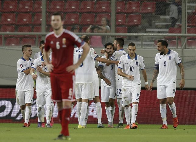 Greece's Panagiotis Kone (C) is hugged by his teammates after his goal during their Euro 2016 group F qualifying soccer match against Hungary at the Karaiskakis stadium in Piraeus, near Athens, Greece, October 11, 2015. REUTERS/Alkis Konstantinidis