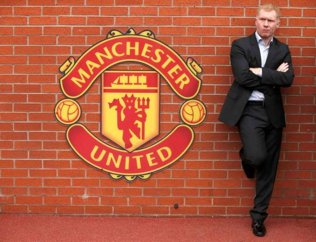 Former Manchester United player Paul Scholes stands next to a team emblem before their English Premier League soccer match against Everton at Old Trafford in Manchester, northern England October 5, 2014. REUTERS/Phil Noble