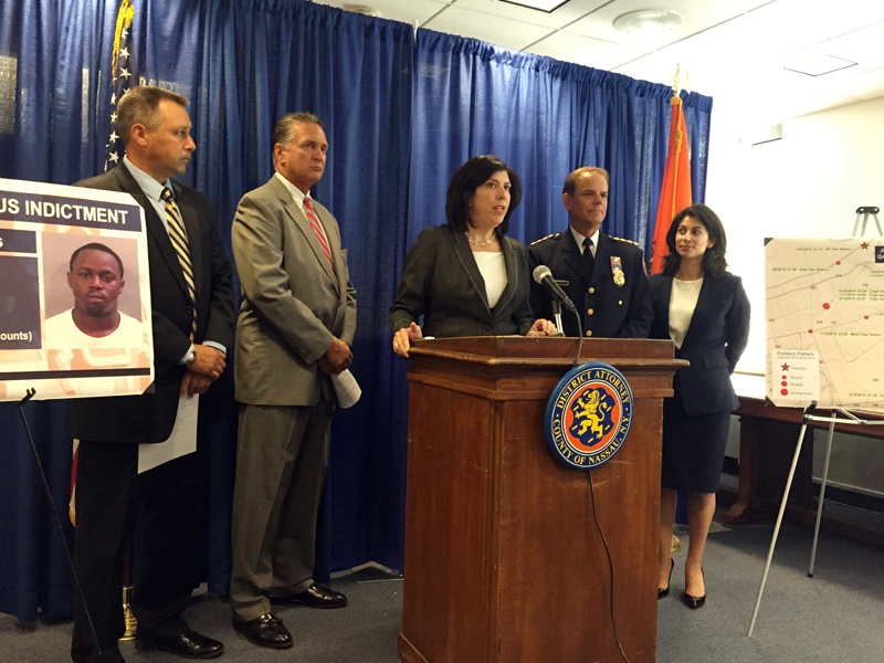 In this Aug. 12, 2015 photo, acting Nassau County District Attorney Madeline Singas, center, details the arrest of Jason Golson-Orelus, at the Nassau County District Attorneyu0092s Office in Mineola, N.Y.  Golson-Orelus is accused of committing nearly a dozen armed robberies across New Yorku0092s Long Island until a stack of bills secretly embedded with a GPS tracking device led to his arrest. (AP Photo/Michael Balsamo)