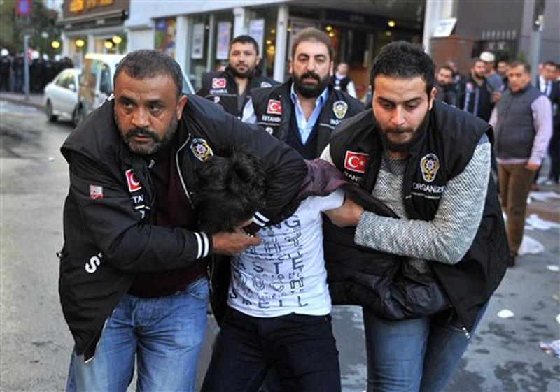 Police detain a protester as they confront protesters near the headquarters of a media company with alleged linked to a government critic, where police enforced a court order to seize the business, in Istanbul, October 28, 2015. Photo: AP