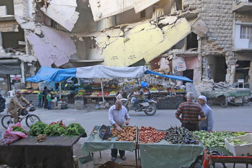 Civilians shop for vegetables and fruits displayed in front of a damaged building in Aleppo's Bustan al-Qasr neighborhood, Syria October 14, 2015. Photo: Reuters