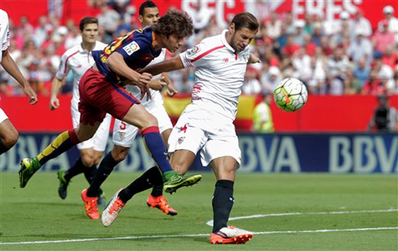 Barcelona's Sergi Roberto (left) and Sevilla's Grzegorz Krychowiak, right, vie for the ball during their La Liga soccer match at the Ramon Sanchez Pizjuan stadium, in Seville, Spain on Saturday, October 3, 2015. Photo: AP