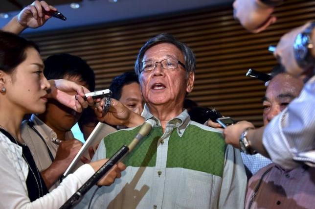 Okinawa Governor Takeshi Onaga (C) is surrounded by reporters after he met with Japanese Prime Minister Shinzo Abe at Abe's office in Tokyo on August 7, 2015. REUTERS/Yoshikazu Tsuno/Pool/Files