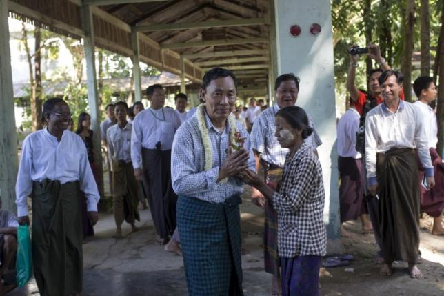 Shwe Mann (C), speaker of lower house of parliament receives flowers from a supporter before he gives a speech inside a monastery compound in his constituency in Phyu, October 17, 2015. REUTERS/Minzayar