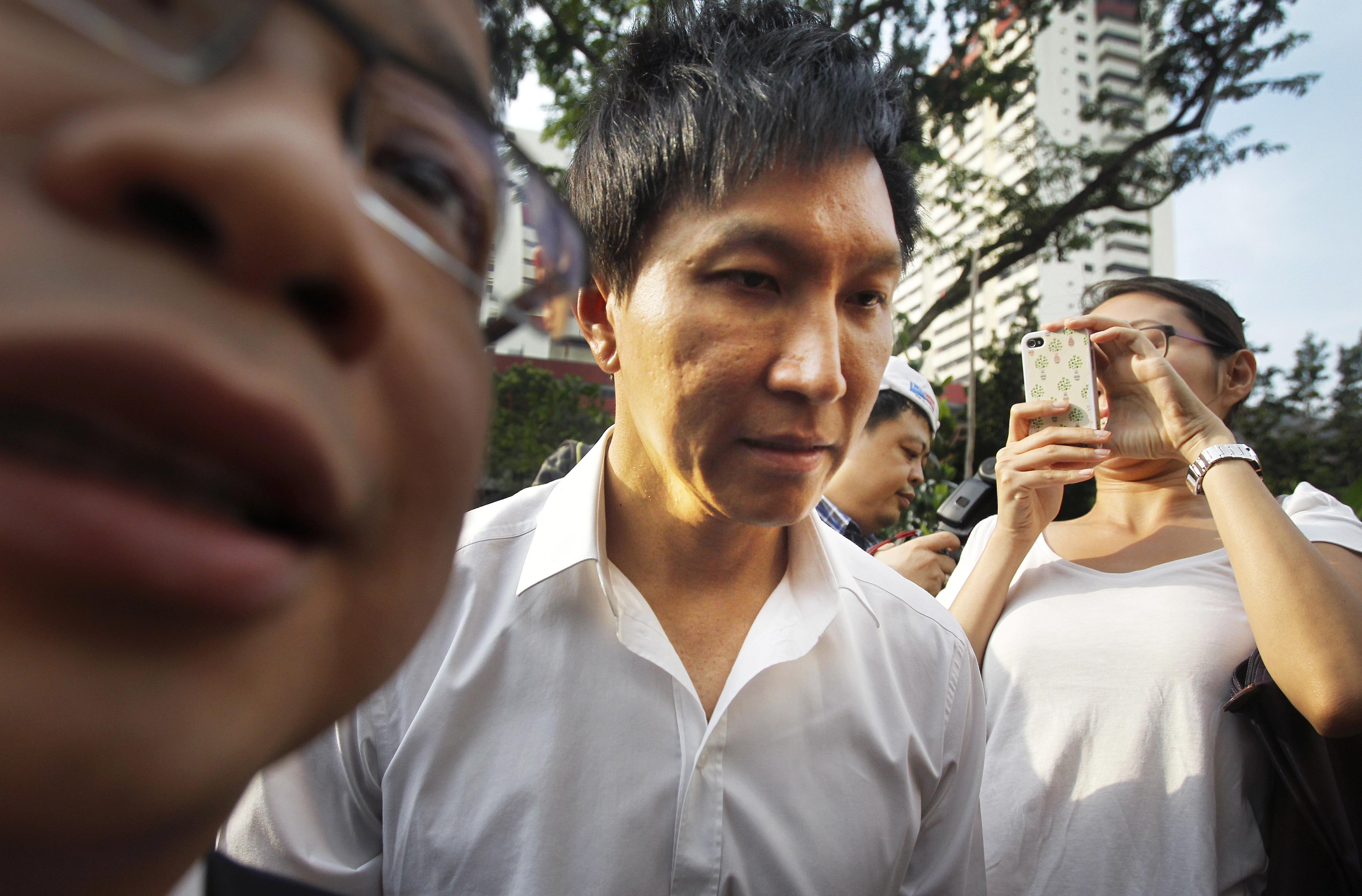 In this July 12, 2012, photo, City Harvest Church founder Kong Hee (centre) is surrounded by the media as he arrives at the Subordinate Courts in Singapore. Photo: AP/ File
