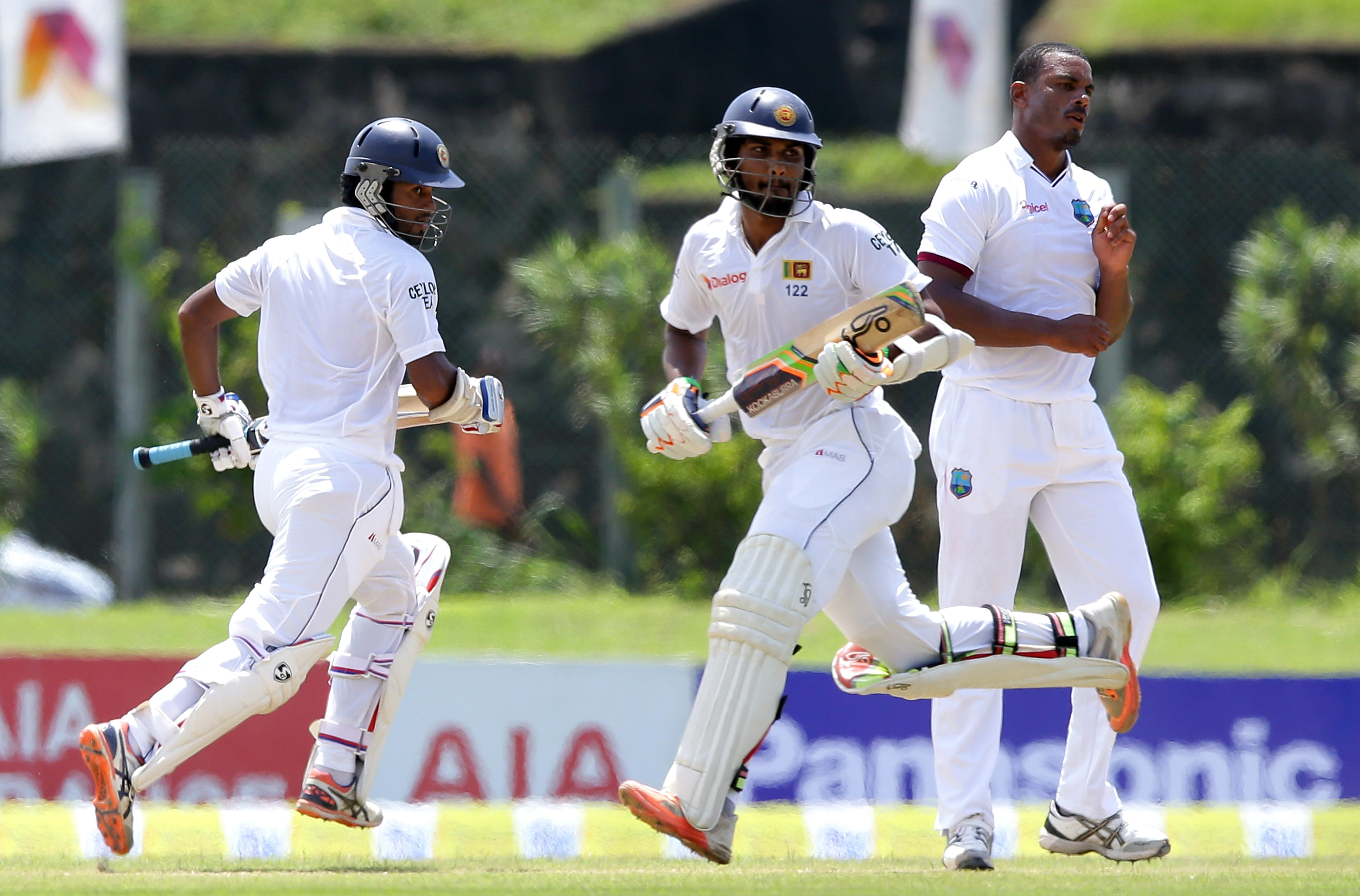 Sri Lankan cricketers Dimuth Karunarathne, left, and Dinesh Chandimal run between the wickets as West Indies' bowler Shannon Gabriel watches during the second day of the first test cricket match against West Indies in Galle, Sri Lanka, Thursday, Oct. 15, 2015. ( AP Photo/ Pamod Nilru )