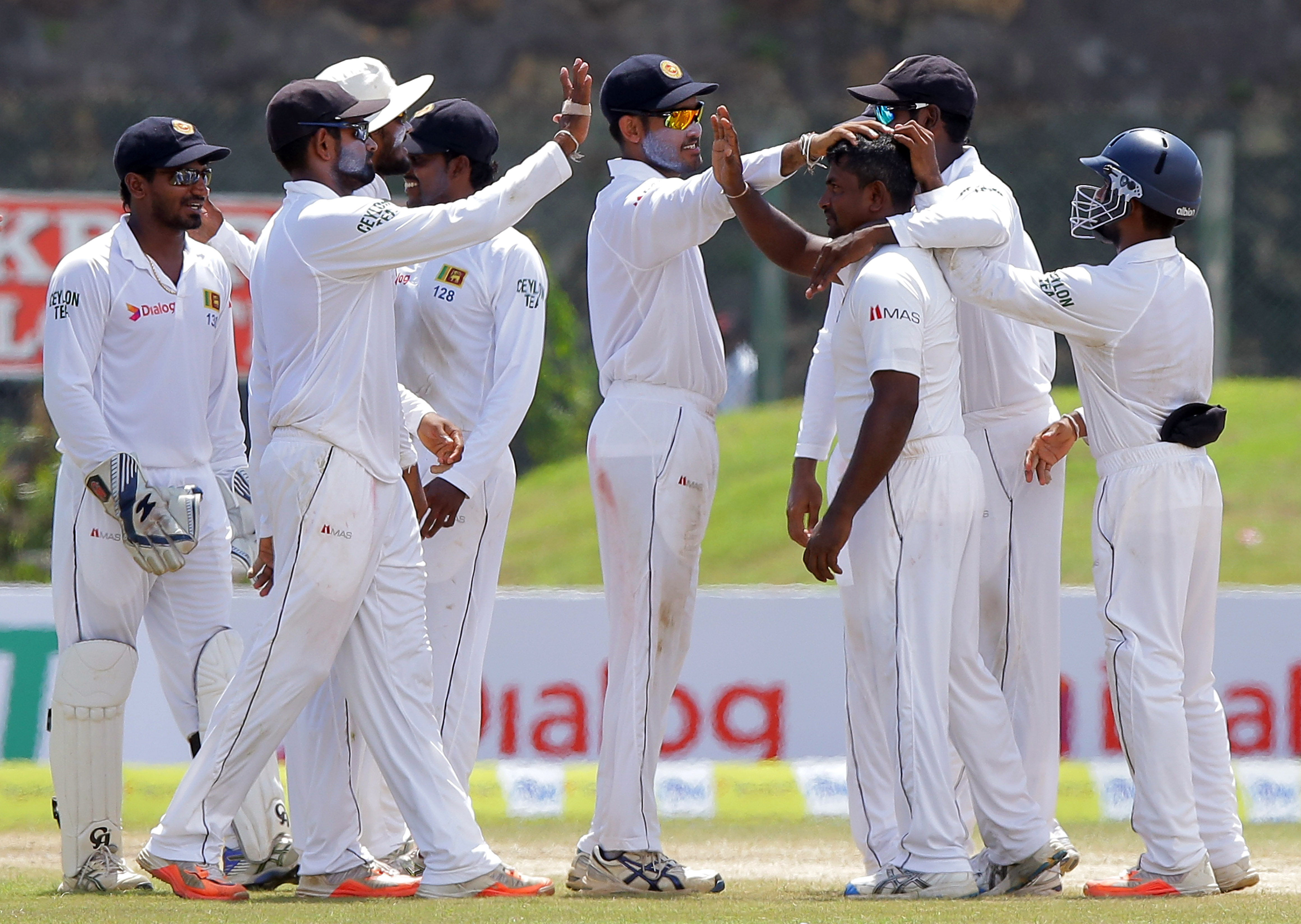 Sri Lankan cricketers congratulate bowler Rangana Herath, without cap, for the dismissal of West Indies' Kemar Roach during the fourth day of the first test cricket match in Galle, Sri Lanka, Saturday, Oct. 17, 2015. ( AP Photo/ Pamod Nilru )