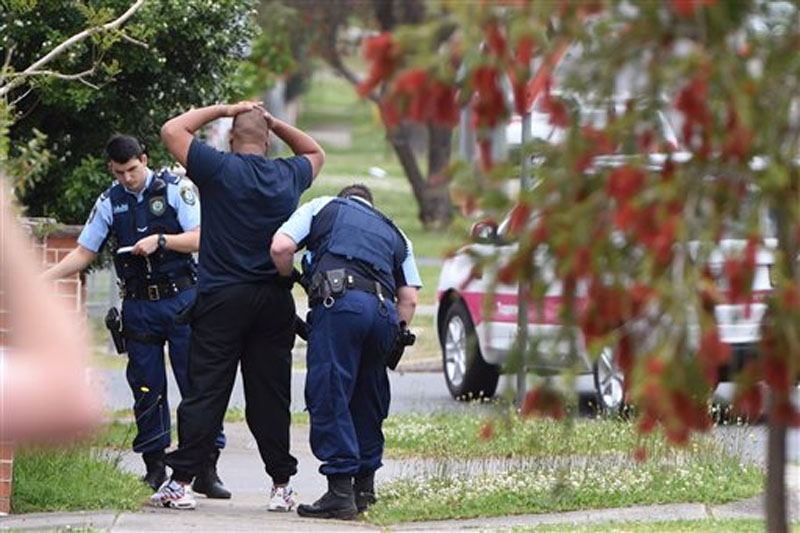 Police pull over and search a man and his vehicle near a house which was raided earlier Wednesday morning on Bursill Street at Guildford in Sydney's west on October 7, 2015. Photo: AP