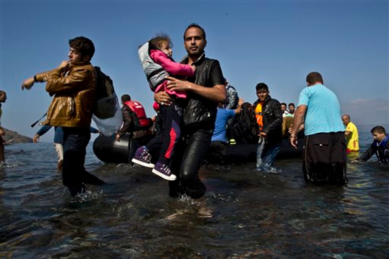 A Syrian refugee man carrying his daughter rushes to the beach as he arrives on a dinghy from the Turkish coast to the northeastern Greek island of Lesbos on Sunday, Oct. 4 , 2015. Photo: AP