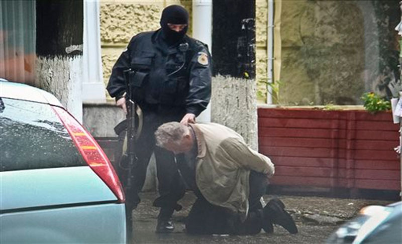 Teodor Chetrus is detained by a police officer in Chisinau, Moldova during a uranium-235 sting operation on June 27, 2011. Photo: AP