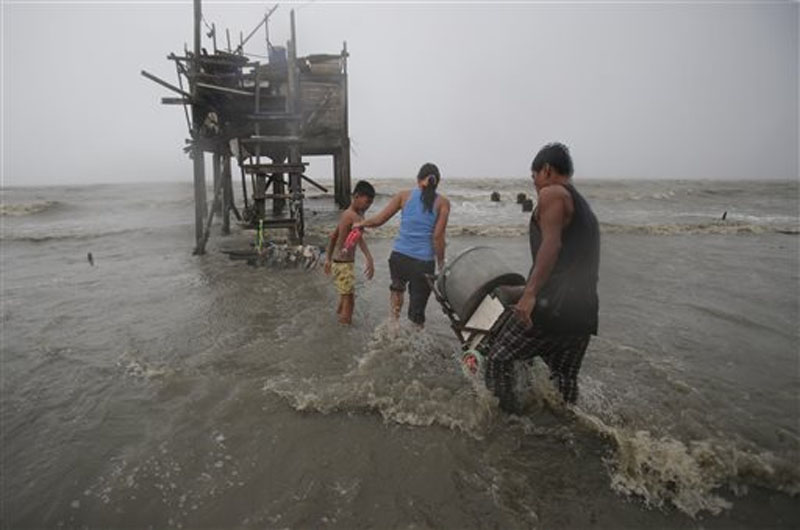 Residents carry their belongings towards their house on stilts as strong winds and rains caused by Typhoon Koppu hits the coastal town of Navotas, north of Manila, Philippines on Sunday, October 18, 2015. Photo: AP