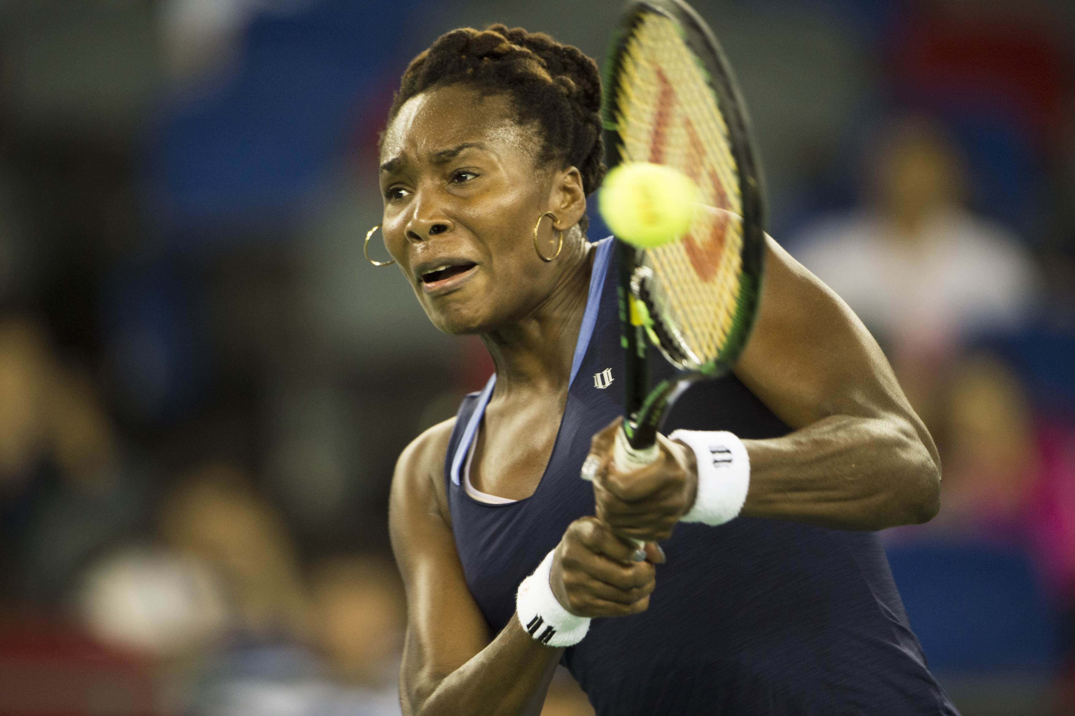 Venus Williams of the US returns a shot to Johanna Konta of Great Britain during the women's singles match on the quarter final of the Wuhan Open tennis tournament in Wuhan, in China's Hubei province on October 1, 2015. AFP PHOTO / FRED DUFOUR