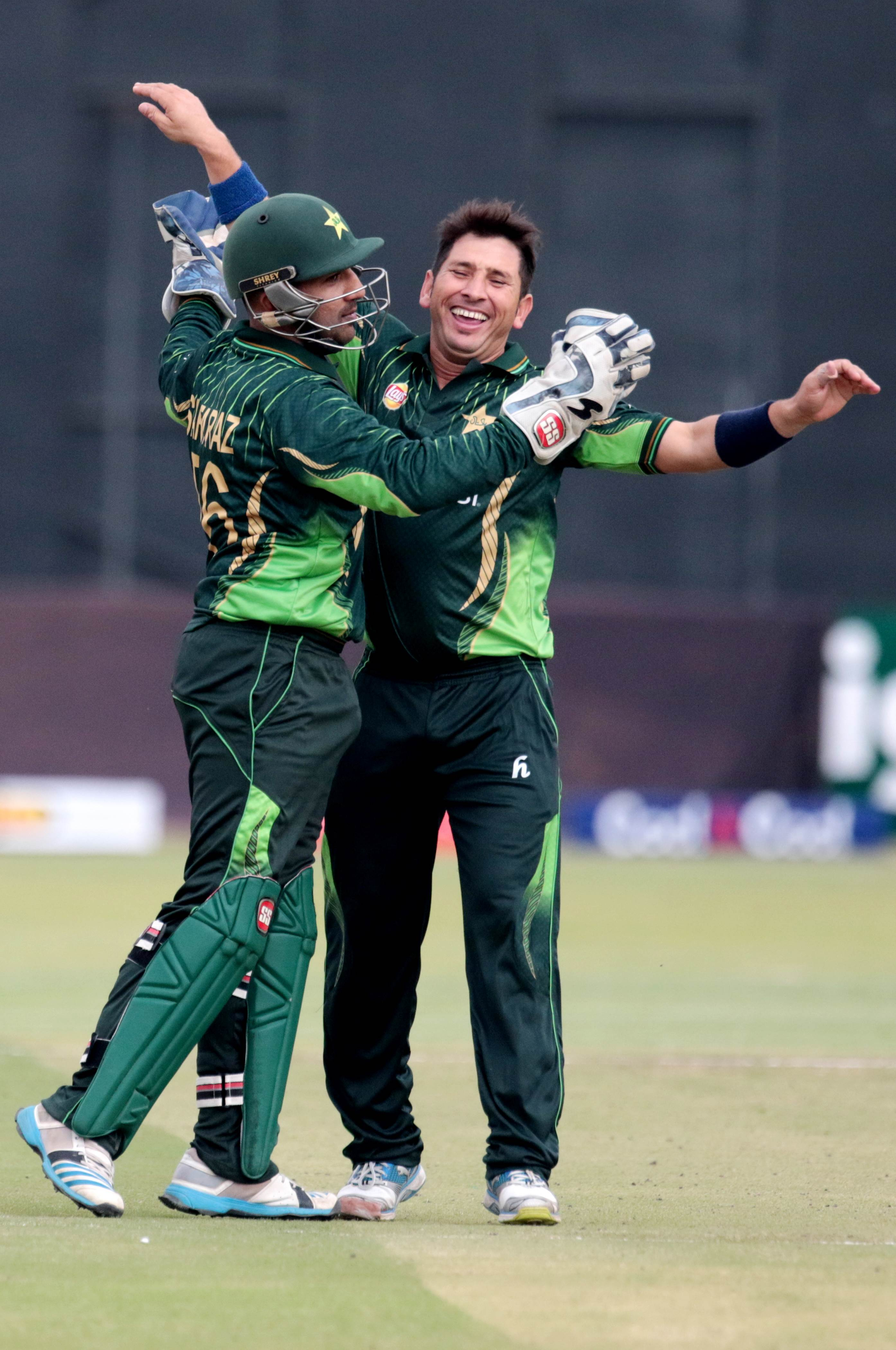 Pakistani bowler Yasir Shah (R)celebrates a wicket with wicketkeeper Sarfraz Ahmed during the first in a series of three One Day International (ODI) cricket matches between Pakistan and hosts Zimbabwe at the Harare Sports Club, in Harare on October 1, 2015.  AFP PHOTO / JEKESAI NJIKIZANA
