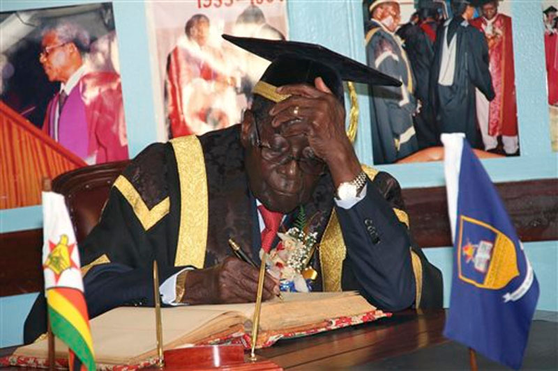 Zimbabwean President Robert Mugabe writes his comments in a visitors' book at the University of Zimbabwe in Harare on Friday October 2, 2015. Photo: AP