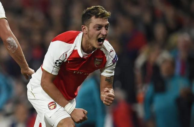 Mesut Ozil celebrates with team mates after scoring the second goal for Arsenal in UEFA Champions League Group Stage  Group F match at Emirates Stadium, London. Reuters / Dylan MartineznLivepicnEDITORIAL USE ONLY.