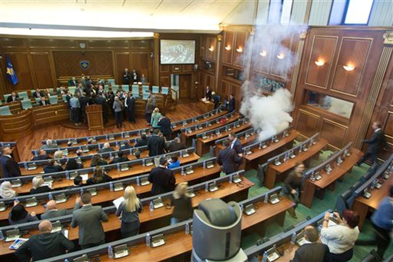 Kosovo lawmakers empty the chamber of Parliament as smoke billows from a tear gas canister thrown by opposition lawmakers in Kosovo disrupting Parliament's session, in the capital Pristina on Thursday, October 15, 2015. Photo: AP