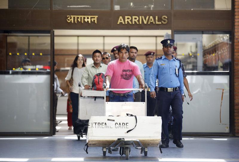 Dolakh Dangi (C), nephew of the world's shortest man Chandra Bahadur Dangi, walks with Chandra Bahadur's body in a box, at the Tribhuvan International Airport in Kathmandu, on Friday, October 2, 2015. Photo: Reuters