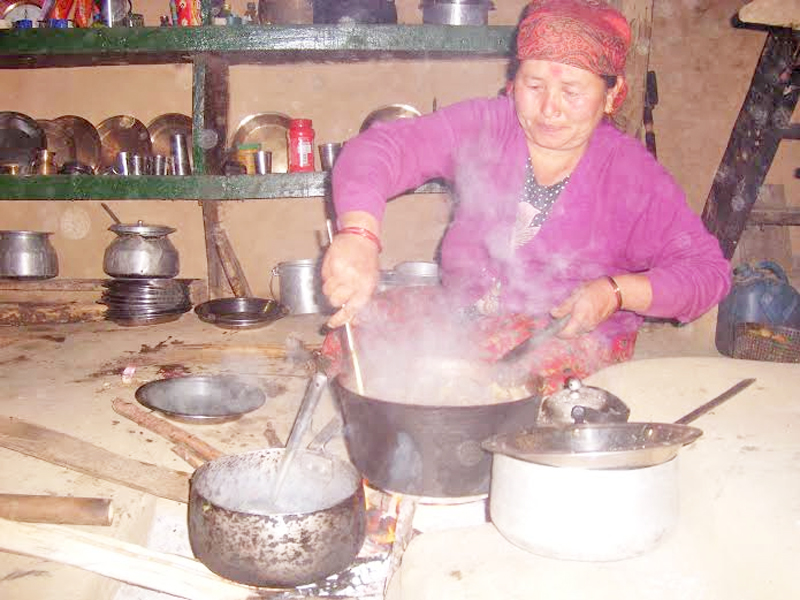 A woman cooking meat in firewood at Taprang village of Sildajure Village Development Committee on Tuesday, October 06, 2015. Photo: Rup Narayan Dhakal